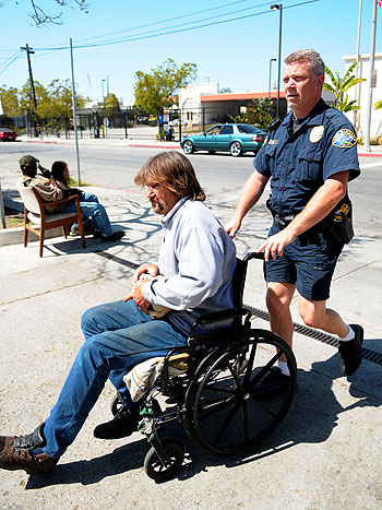 Santa Barbara police Tactical Officer Keld Hove helps a homeless man to Casa Esperanza for lunch Sunday. Expanded cooperation between police and nonprofit organizations are part of Santa Barbara's 12-point approach on homelessness, which officials will be evaluating Tuesday.