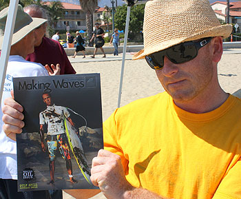 Scott Bull, of Surfrider Foundation's Santa Barbara chapter, shows off a posed photo of a surfer covered in oil.