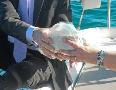 With great care, ashes are handed off to be scattered at sea ...