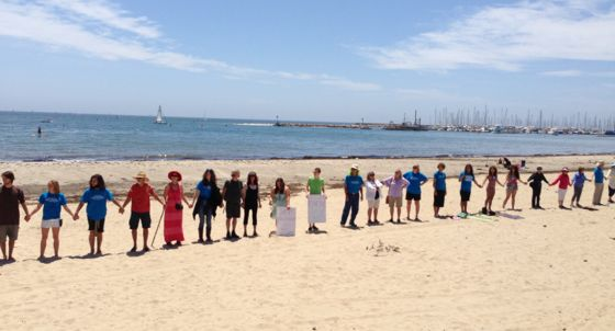 <p>More than 100 people joined hands Saturday for the Water Guardians&#8217; 'Hands Across the Sand' rally.</p>