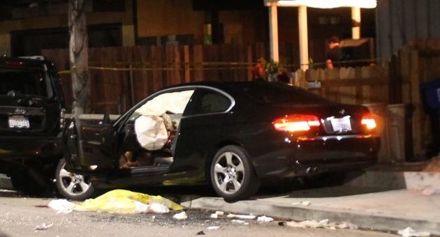 A BMW sedan sits wrecked on an Isla Vista sidewalk after the driver — who allegedly gunned down six people during a blocks-long shooting rampage Friday night — was fatally shot by Santa Barbara County sheriff's deputies in the 6500 block of Del Playa Drive. (Urban Hikers photo