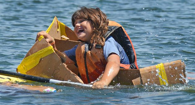 A cardboard boat captain is all smiles Saturday as she remains with her ship as it sinks in the Santa Barbara harbor during the annual family event. (Mike Eliason / Noozhawk photo)