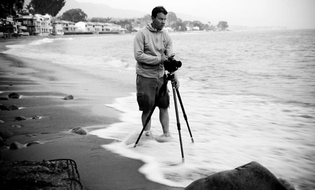 <p>In the evening dusk and with the tide swirling about his feet, photographer Nick Price readies his camera gear for some wave action at Montecito&#8217;s Miramar Beach.</p>