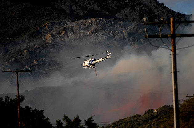 Santa Barbara County Fire Helicopter 308 makes a water drop during the 2009 Jesusita Fire in the Santa Barbara foothills. The helicopter, which is also used for rescues, apparently encountered mechanical difficulties when it was dispatched Sept. 14 to assist a hiker. The woman died before the aircraft's arrival. (Lara Cooper / Noozhawk file photo)