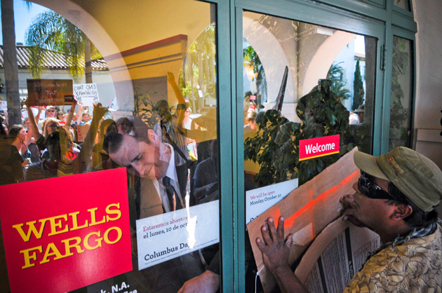<p>A Wells Fargo Bank manager locks the front door as protesters mass outside the building at 1036 Anacapa St. in Santa Barbara on Saturday.</p>