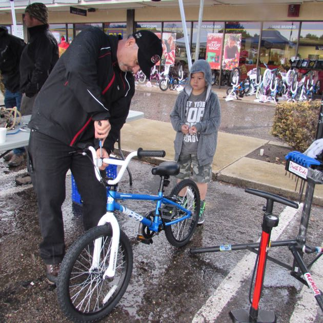 Village Dirtbag member Scott Penn adjusts Ethan Chang's new bike during the mountain bicycling club's 10th year of presenting new bikes to children at Vandenberg Air Force Base.