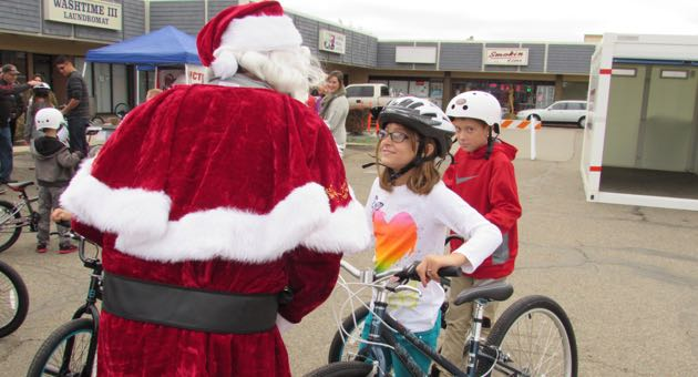 Abbie Carr, 10, visits with Santa Claus after receiving her bike and helmet Saturday. (Janene Scully / Noozhawk photo)