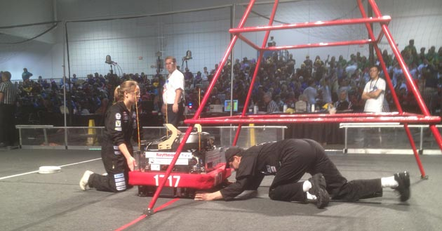 Olivia Hart, one of Team 1717's drivers, and Dos Pueblos Engineering Academy director Amir Abo-Shaeer adjust PenguinBot VIII just prior to a match.