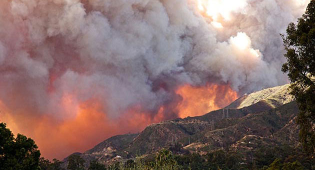 Smoke from the eastern edge of the 2009 Jesusita Fire piles up and over the ridge of upper Rattlesnake Canyon as flames march toward Montecito foothills burned six months before in the 2008 Tea Fire. (Will Macfadyen / Noozhawk file photo)