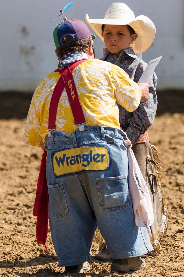 "Famed rodeo clown Charlie ""Too Tall"" West delivers a gift certificate to the day's winner of the Best Dressed Cowboy contest."