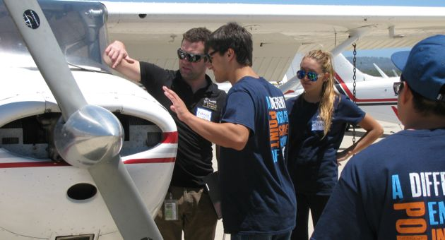 <p>Above All Aviation flight instructor Patrick Corrigan, far left, shows students around one of the Cessna 172s they piloted Friday, including how to check the oil and look for signs of damage. &#8220;Life is like flight,&#8221; Corrigan told the teens. &#8220;When things are stable they&#8217;re great, but when they aren&#8217;t, that&#8217;s where the work comes in.&#8221;</p>