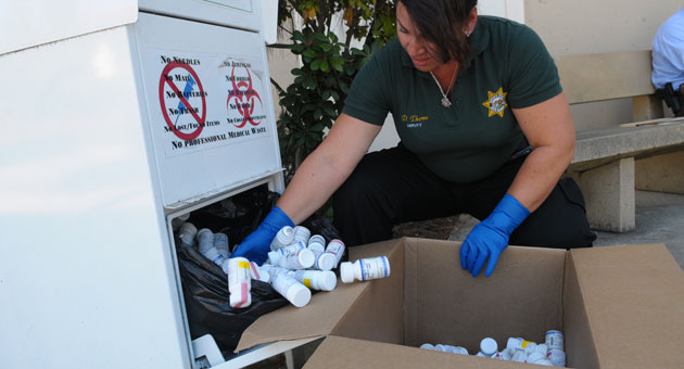 Santa Barbara County sheriff's Deputy Desiree Thorne empties the prescription drug drop box outside department headquarters at 4436 Calle Real. The Sheriff's Department has eight drop boxes at substations around the county. (Lara Cooper / Noozhawk file photo)