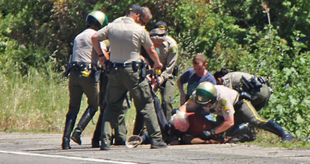 Santa Barbara County sheriff's deputies wrestle a suspect to the ground along Highway 101 near Goleta after he allegedly threatened them with a knife. (John Palminteri / KEYT News photo)