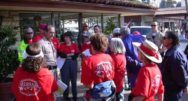 Members of the Montecito Emergency Response and Recovery Action Group, or MERRAG, get a briefing from law enforcement personnel outside Montecito Village Hardware. (MERRAG file photo)