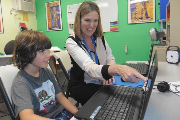Mary Beth Adams, United Learning Center manager, helps a student with a program.