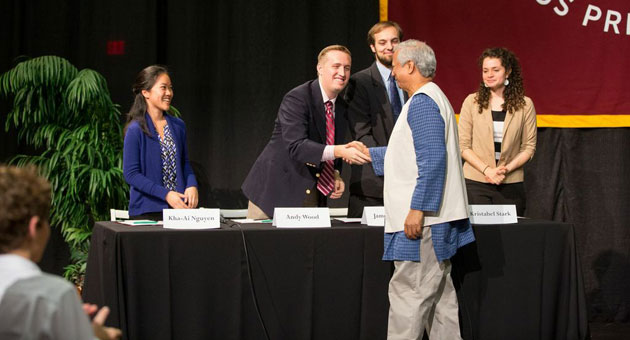 After a vigorous panel discussion at Westmont College's Friday convocation, microfinance pioneer Muhammad Yunus greets the students who posed the questions to him. From right are Kristabel Stark, James Sievers, Andy Wood and Kha-ai Nguyen. (Brad Elliott / Westmont College photo)