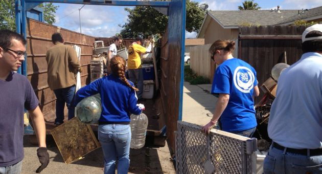 Volunteers cart trash and debris into a roll-off container outside a Santa Maria home, as part of the seventh Serve Santa Maria Day. (City of Santa Maria photo)