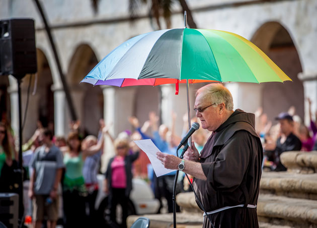 Father Larry Gosselin of the Santa Barbara Mission leads a prayer for rain, while holding an umbrella for good measure.