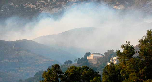Smoke from the 2009 Jesusita Fire lingers above homes north of Foothill Road in Santa Barbara. Under a new state law, all properties north of Cathedral Oaks, Foothill, Sycamore Canyon and East Valley roads will be required to pay a $150 fee that will go to support CalFire and not local fire agencies. (Lara Cooper / Noozhawk file photo)