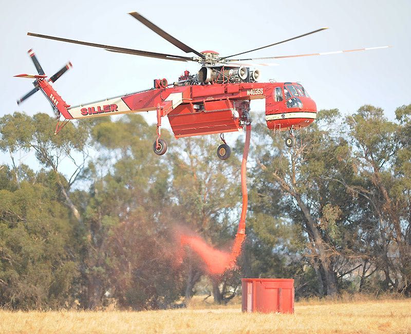 "A Sikorsky S-64E Skycrane ""dips"" from a portable fire retardant tank at a temporary helittack base in Goleta during the Sherpa Fire."