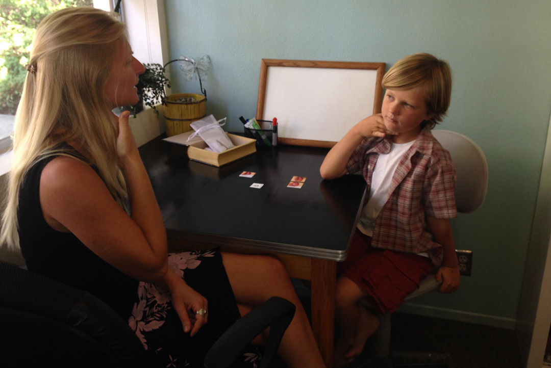 Lori Henning teaches Logan, 5, how to listen to and pronounce words.