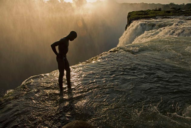 With the 355-foot-high drop of Victoria Falls just inches away, a swimmer stands at the lip of a hidden pool accessible only when the Zambezi River runs low. (Annie Griffiths photo)