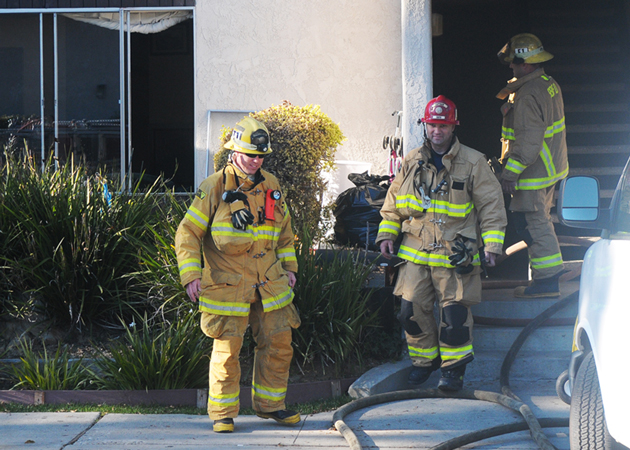 Firefighters mop up Tuesday after a fire at an apartment in the 500 block of Arrellaga Street in Santa Barbara. (Lara Cooper / Noozhawk photo)
