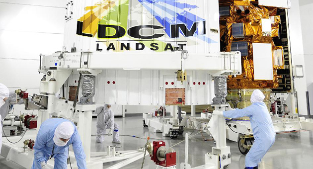 Technicians encapsulate the NASA's Landsat Data Continuity Mission (LDCM) satellite in its payload fairing in the Astrotech processing facility at Vandenberg Air Force Base last month. The satellite is scheduled to be launched into space Monday aboard an Atlas rocket. (NASA photo)
