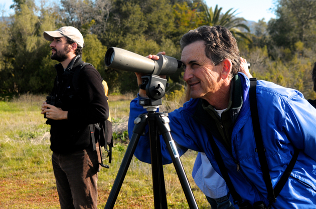 <p>Birder Jerry Rounds peers through a scope during Saturday&#8217;s bird count, as Jeff Simeon watches nearby with binoculars.</p>