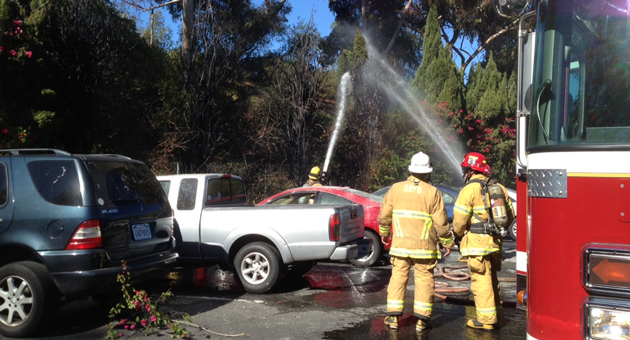 Firefighters extinguish a vegetation fire that damaged four vehicles at Bishop Diego High School in Santa Barbara on Monday. Officials said the blaze was deliberately set. (Santa Barbara Fire Department photo)