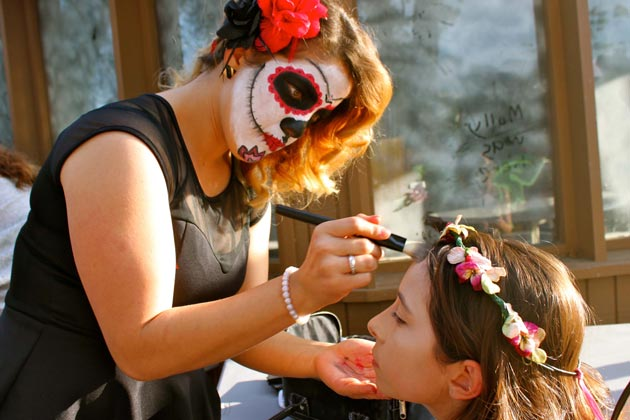 Professional make-up artists prep more than 70 volunteers who act as costumed characters for Boo at the Zoo.