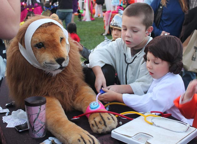 Children give a stuffed lion a veterinary exam as part of the Boo at the Zoo celebration.