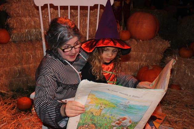 Mother Goose reads to children at Boo at the Zoo.