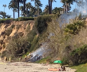 Firefighters battle a vegetation fire that broke Monday on a bluff along Butterfly Beach in Montecito. (John Palminteri / KEYT News photo)