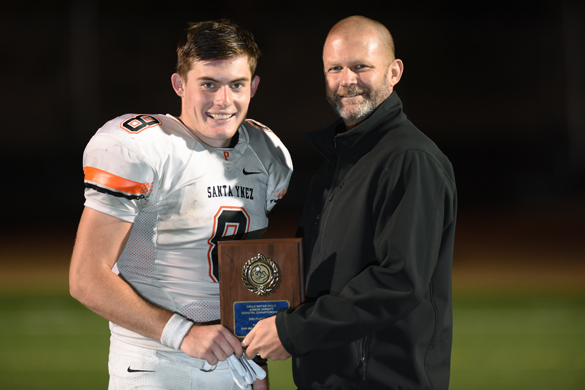 Santa Ynez quarterback Michael Mccoy (left) stands with Pirates Principal Mark Swanitz after receiving the Norm Clevenger Player of the Game Award.