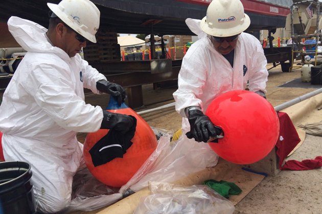 Crew members clean equipment used in the Refugio oil spill response at a decontamination station in Ventura on Sunday. Crew members wear safety equipment to protect from hazardous materials and to prevent contaminants from leaving the decontamination zone.