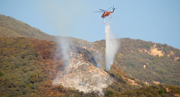 A helicopter makes a water drop on a fire that burned 3 acres along the Cold Springs Trail above Montecito on Tuesday. (Brad Elliott/Westmont College photo)