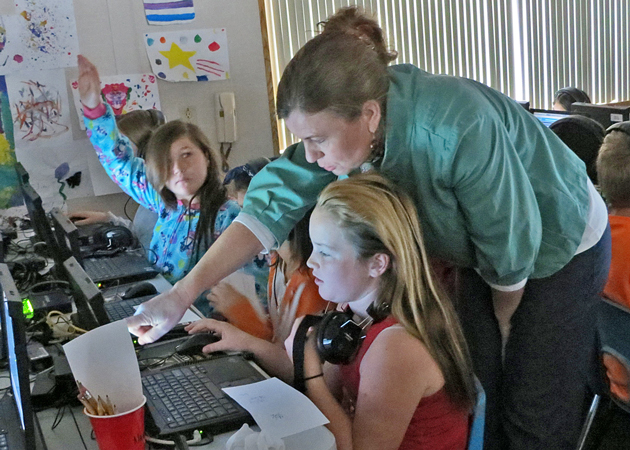<p>Kathleen Stevenson assists Ralph Dunlap Elementary School students using Compass Learning, an online teaching tool that students at the Orcutt campus were encouraged to access over winter break.</p>