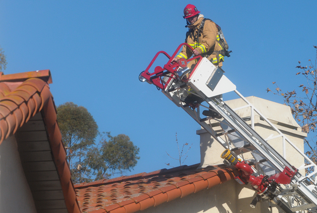 A firefighter uses a ladder truck to access the upper level of a Montecito condominium that caught fire Wednesday, apparently after an explosion tied to a natural-gas leak. (Lara Cooper / Noozhawk photo)