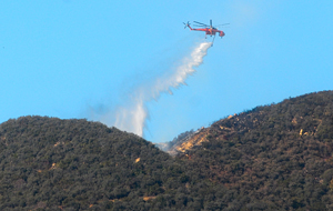 A helicopter makes a water drop on the Cold Fire Tuesday above Montecito. (Lara Cooper / Noozhawk photo)