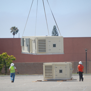 Two workers stand by as an air-conditioning unit is lowered into place by a helicopter Wednesday at Dos Pueblos. (Barbara Keyani photo / Santa Barbara Unified School District)