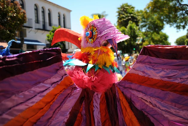 A performer wearing a colorful bird costume makes her way to the starting line for Santa Barbara's annual Summer Solstice Parade on June 23.