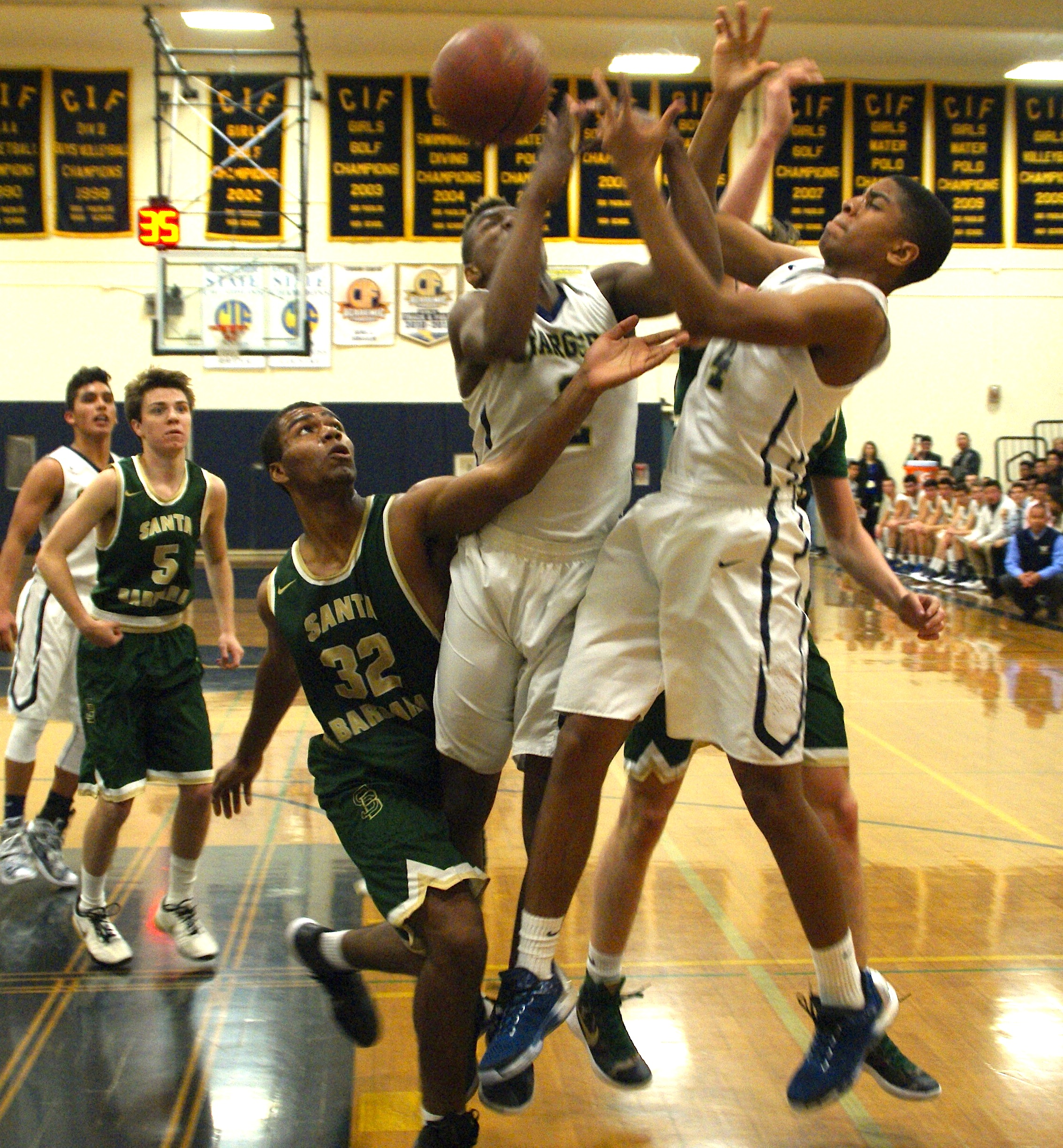 Santa Barbara's Ben Clay waits for the ball to drop into his hand after Marcellous Gossett and Cyrus Wallace of Dos Pueblos fail to come up with a rebound.