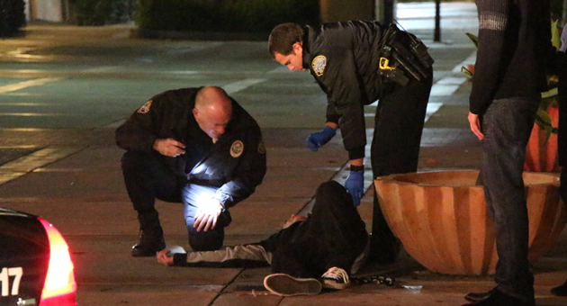 Santa Barbara police officers tend to a man who was stabbed early Saturday in downtown Santa Barbara. (John Palminteri / KEYT News photo)