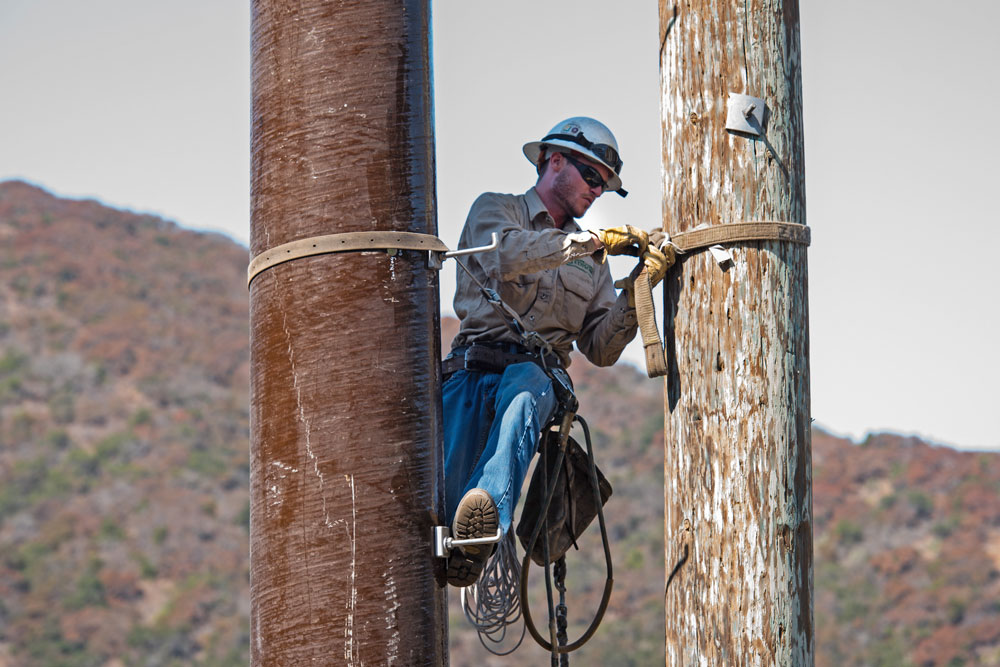 Utility worker on power poles