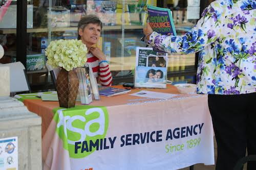 A representative from Family Service Agency discusses nonprofit work with an attendee of the 2015 Caring & Sharing event. FSA was 1 of 63 nonprofits that participated in 2015.