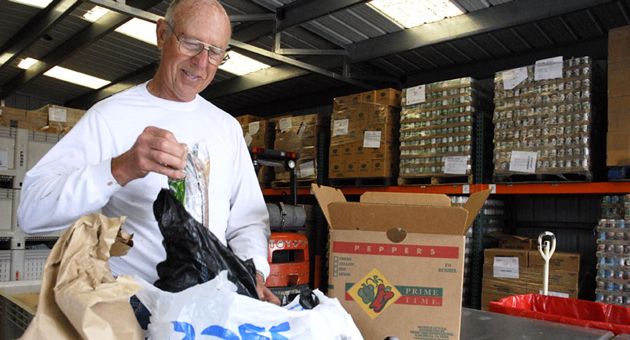 <p>A volunteer helps out at the Foodbank of Santa Barbara County, one of many local organizations seeking volunteers and support during the holiday season.</p>