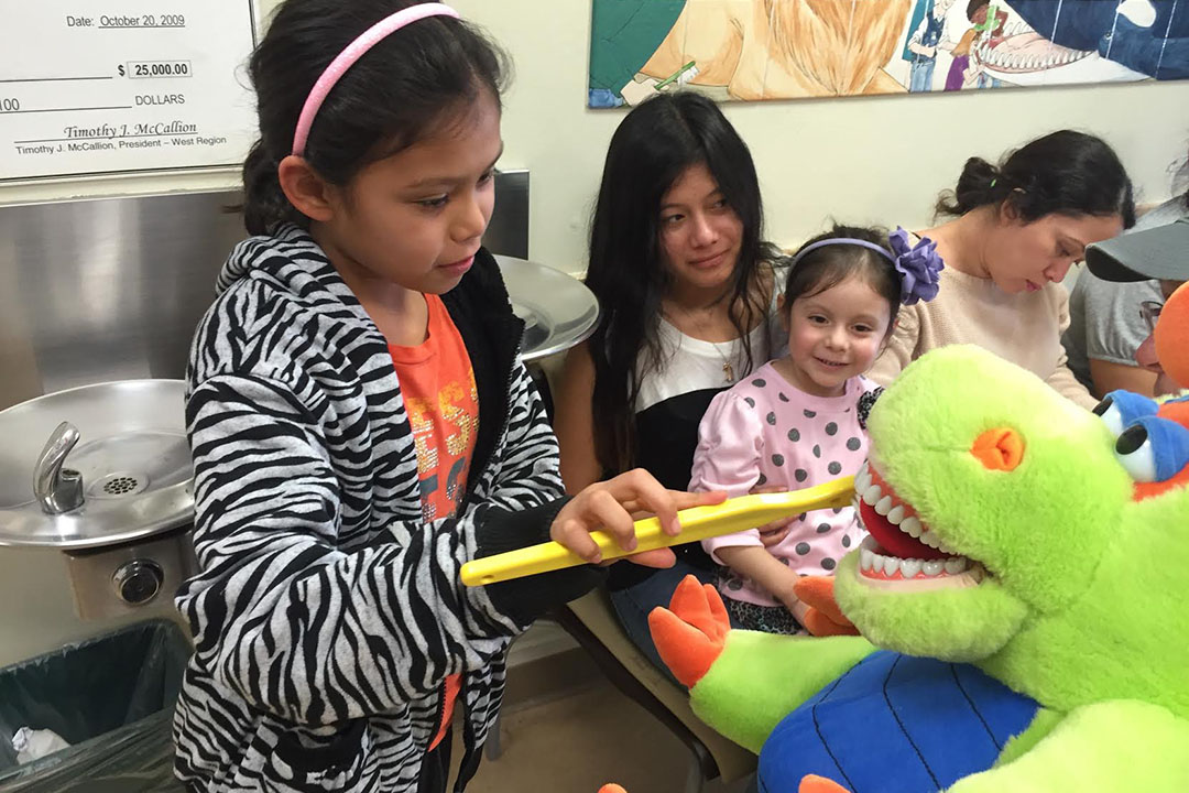 A young girl practices proper brushing techniques on puppets during Free Dental Day.