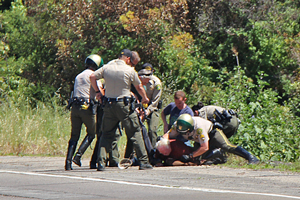 Law enforcement personnel wrestle a suspect to the ground Wednesday afternoon on Highway 101 near Goleta. The suspect allegedly threatened deputies with a knife. (John Palminteri / KEYT News photo)