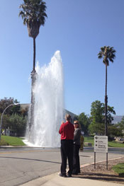 Bystanders view the sheared-off hydrant.